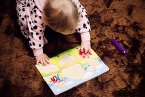 toddler doing a puzzle on the floor