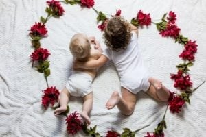 young siblings lying in a flower heart