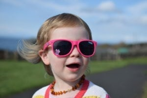 Toddler girl wearing pink sunglasses