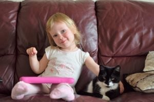 toddler girl cuddling black and white kitten
