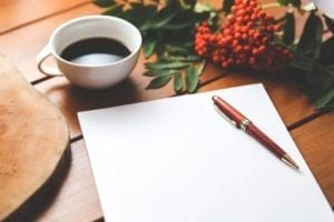coffee cup and pen and paper on a wooden desk with flowers in the background