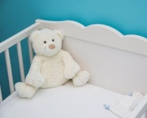 teddy in a white crib