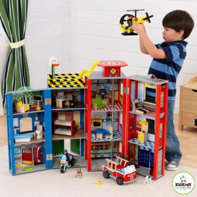 boy playing with a firefighter and police play set