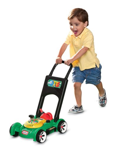 toddler holding a push toy mower