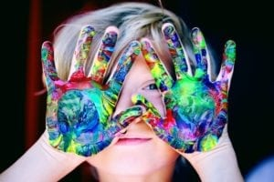 child with colored paints covering their hands
