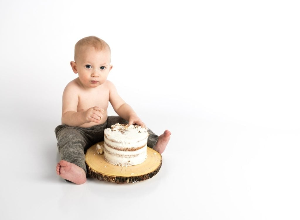 Baby sitting in front of a cake
