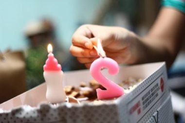 person lighting a candle on 2nd birthday cake