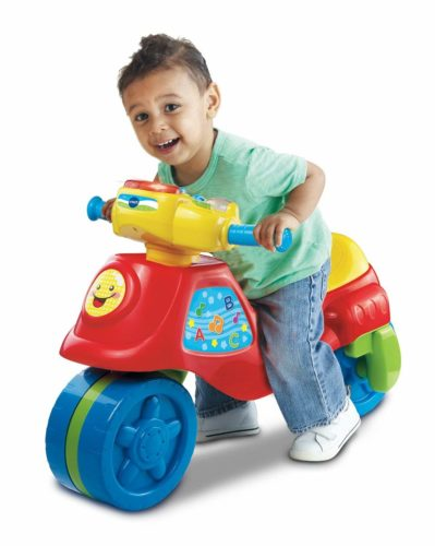 boy riding a toy toddler tricycle