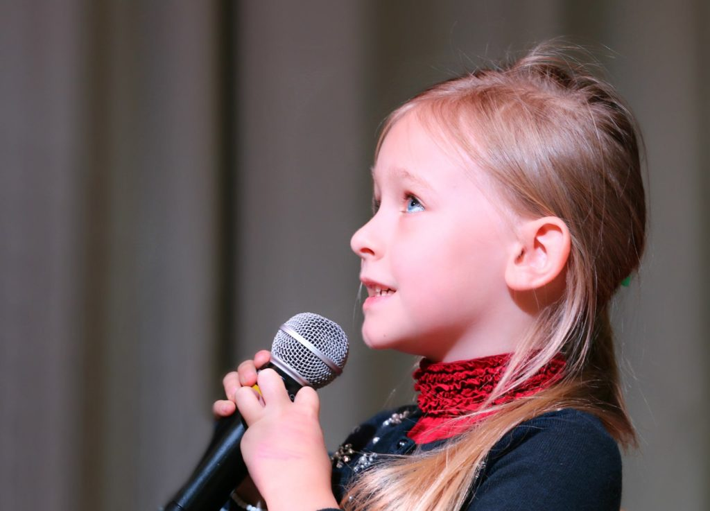little girl singing with a microphone