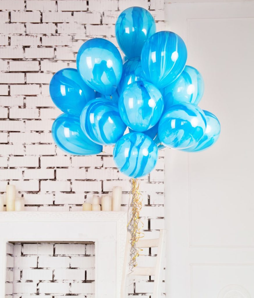 blue balloons against a white brick wall