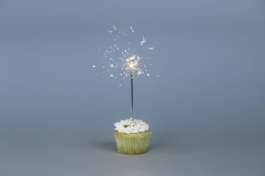 individual cupcake with sparkler against a blue background