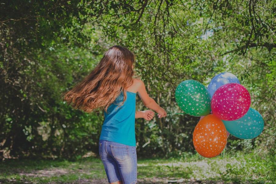 girl holding balloons running
