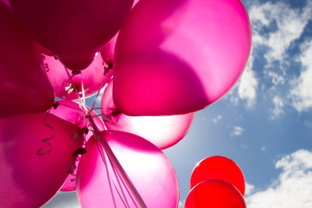 pink balloons from below, against a blue cloudy sky