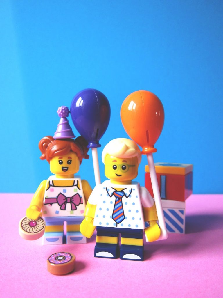 lego minifigures holding balloons with birthday presents