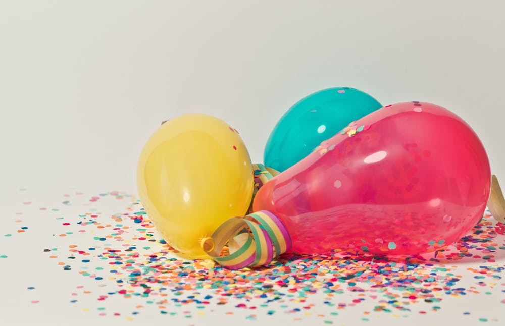red, yellow and blue balloons with confetti