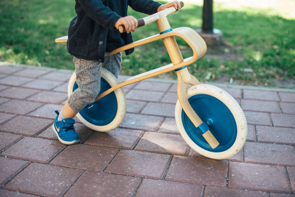 toddler on a wooden balance bike