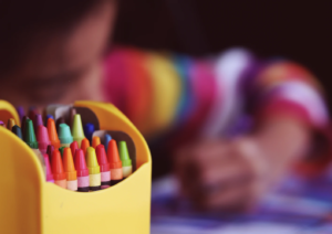 this is an image of crayons and a kid drawing