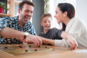 this is an image of a Happy family playing board game at home