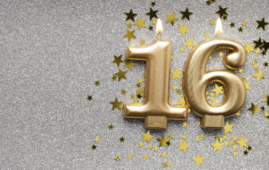 this is an image of a Number 16 gold celebration candle on sparkly star background