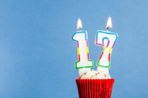 this is an image of a 17th birthday candle in a cupcake against a blue background