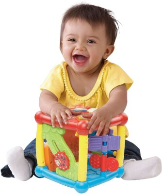 This is an image of a 6 months old child playing with a colorful activity cube.