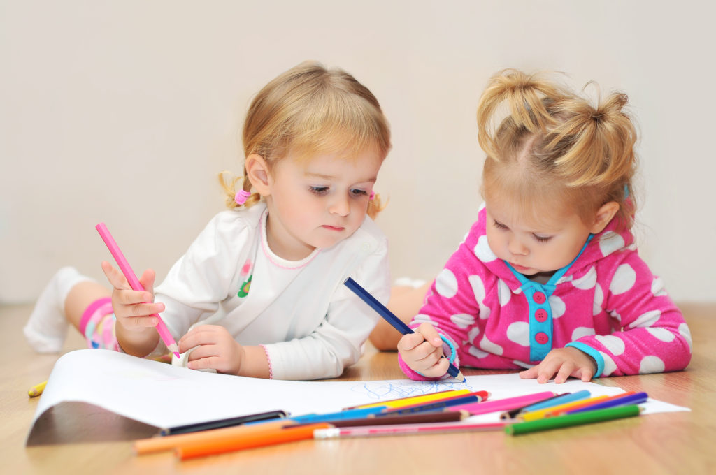 this is an image of two toddlers coloring in