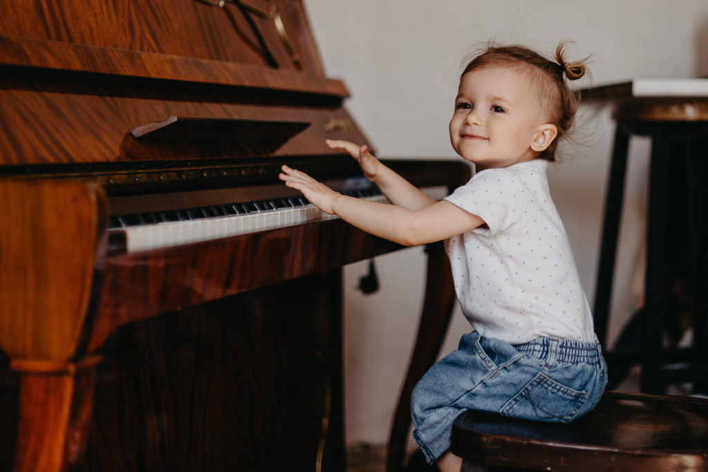 this is an image of a toddler playing a piano