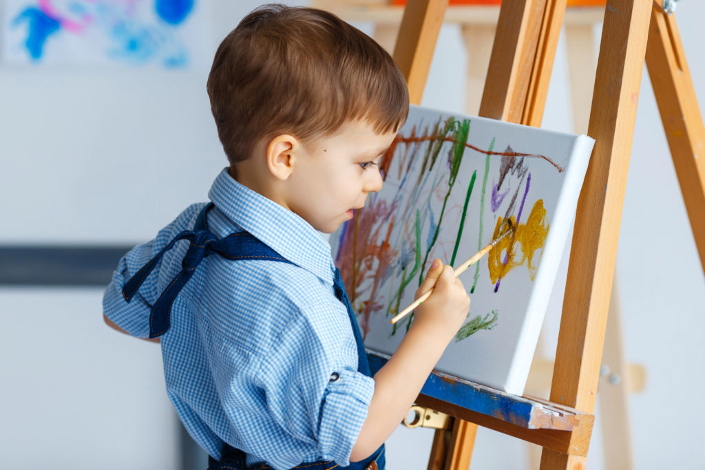this is an image of a 3 year old boy painting on an easel