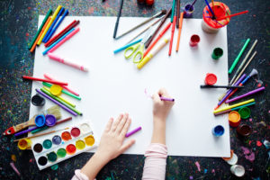this is an image of a child painting with lots of art supplies