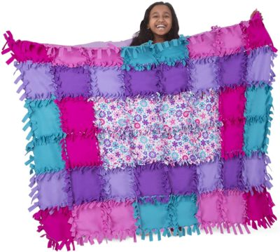 This is an image of a little girls who is holding a fleece quilt.