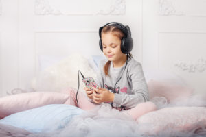 this is an image of a girl listening to an audiobook on her phone