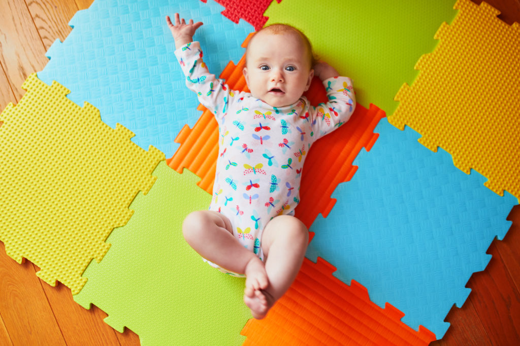 this is an image of a 3 month old baby on a play mat