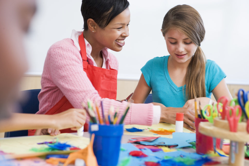 this is an image of a tween girl doing craft with her teacher