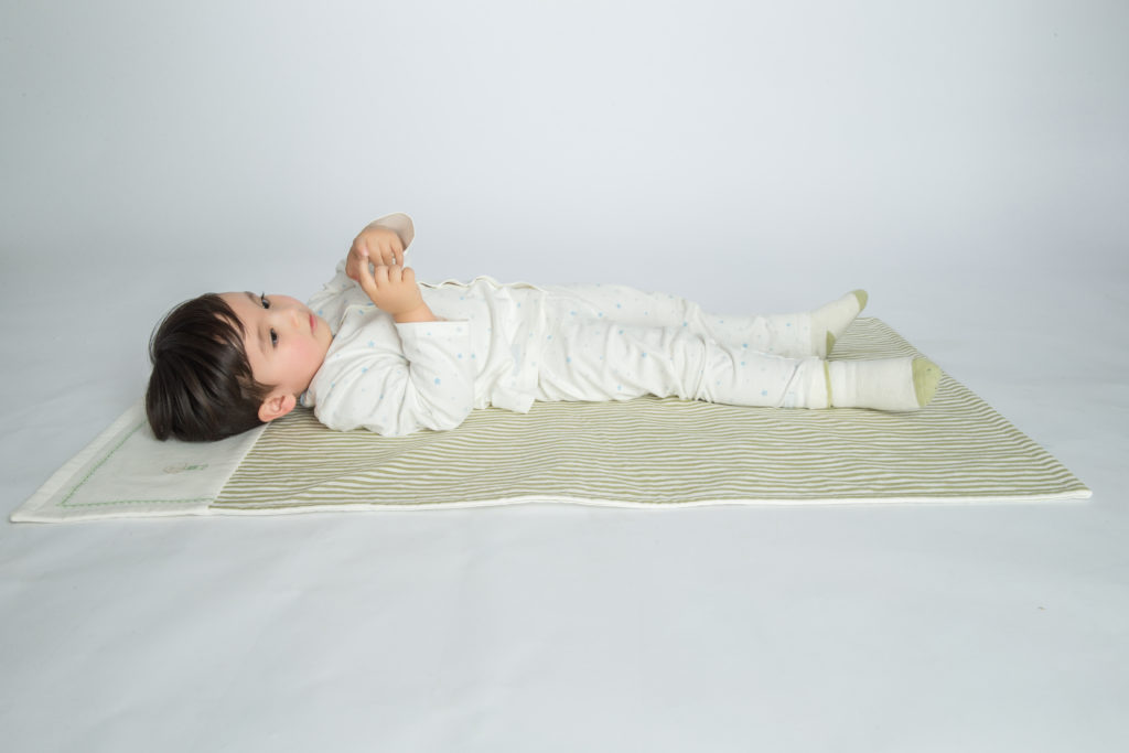 this is an image of a boy lying on a nap mat