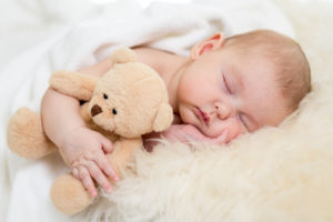 this is an image of a 1 month old baby sleeping with a teddy