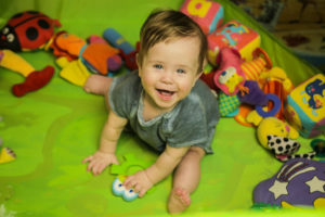 this is an image of a 7 month old boy playing on a mat