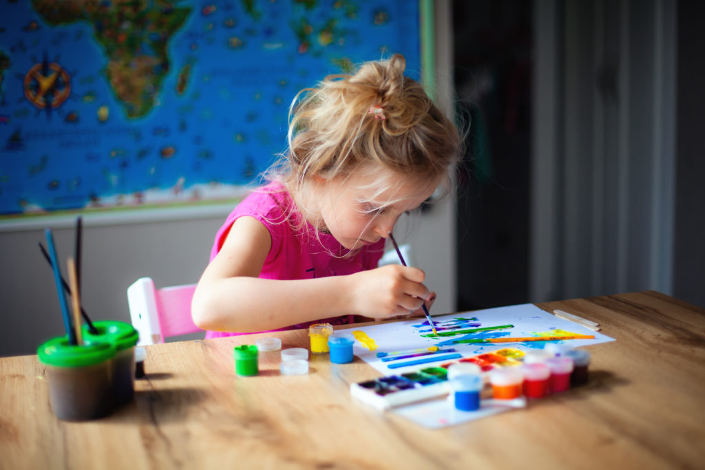 this is an image of a 7 year old girl doing painting craft