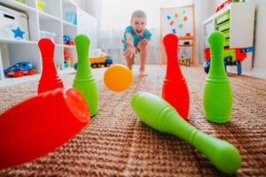 this is an image of a boy playing bowling at home