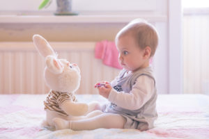 this is an image of a 6 month old girl playing with a soft toy