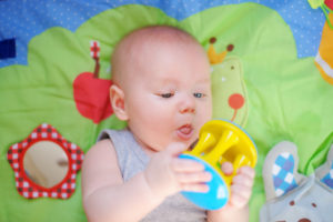 this is an image of a 4 month old baby playing with a toy