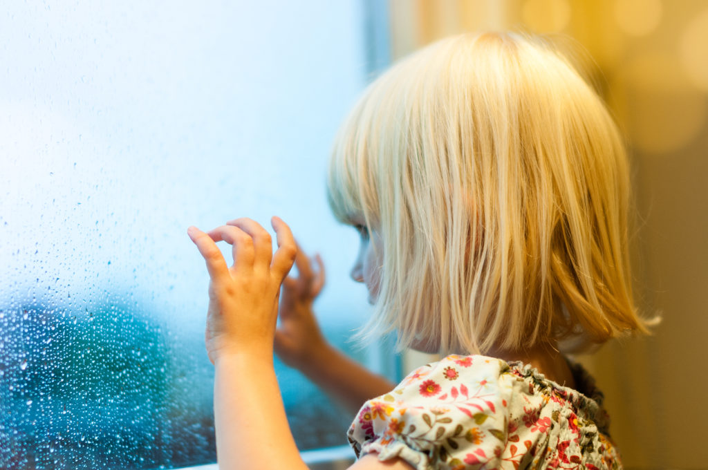 this is an image of a little girl looking out of a rainy window