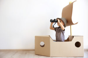 this is an image of a boy playing in a pirate ship made from a cardboard box