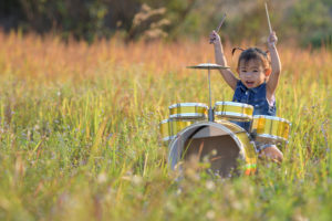 this is an image of a toddler girl playing drums outside