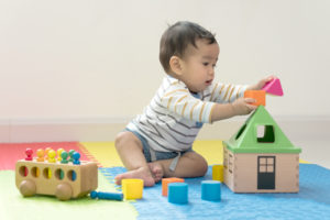 this is an image of a 8 month old baby playing with toys on the floor