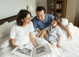 this is an image of a this is an image of a family looking at a photo album on a bed