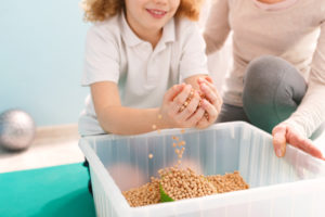 this is an image of a child playing with a sensory box